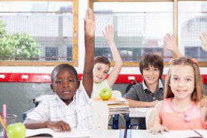 kids in the classroom raising hands
