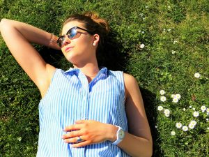 Woman laying in sunlight on grass