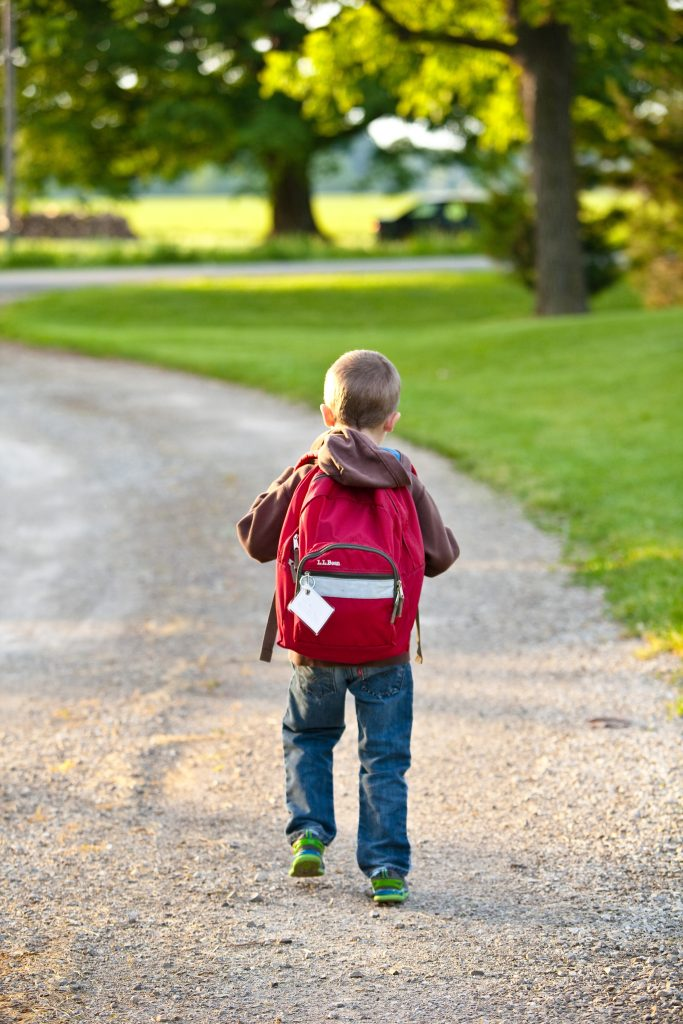 Boy walking down road with red backpack
