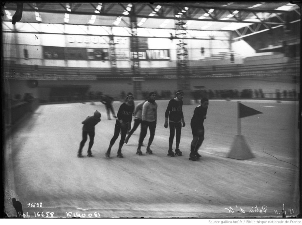Vintage black and white photo of men roller skating
