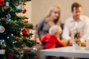Out of focus photo of family by Christmas tree