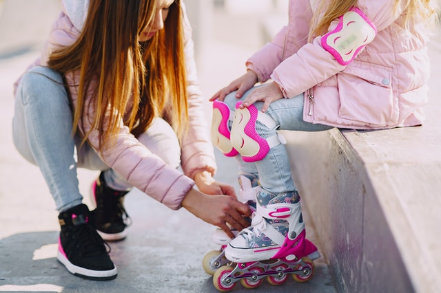 Mom helping daughter with pink inline skates
