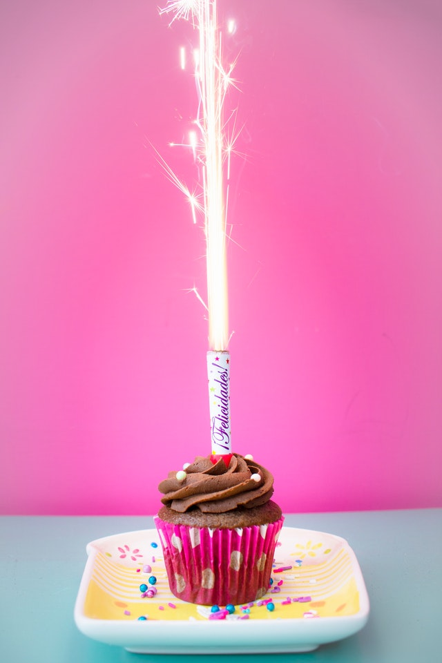 birthday cupcake with sparkler on plate in front of pink wall