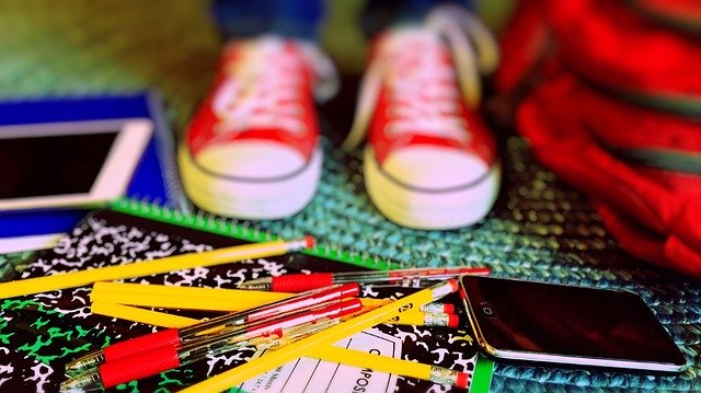 School supplies on ground in front of kid wearing red chucks